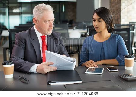 Serious senior boss asking assistant about analytical research while they discussing report at meeting. Concentrated businessman reading magazine together with Hispanic partner. Teamwork concept