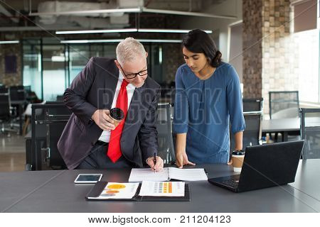 Successful businessman signing document in office. Concentrated young Hispanic female assistant giving papers to boss for signature. On move concept