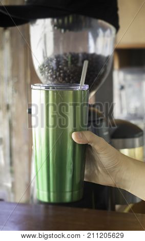Hand holding coffee reuse glass stock photo