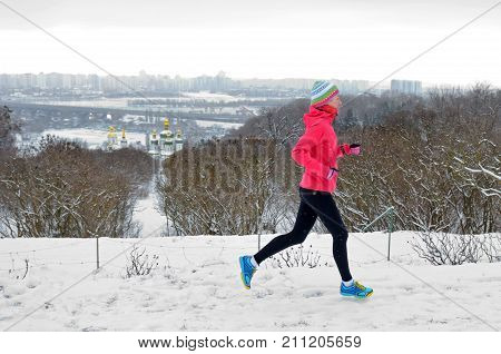 Winter running in park: happy active woman runner jogging in snow with Kyiv city skyline view, outdoor sport and fitness concept