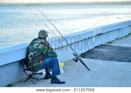 Russia, Saratov - August 9, 2017: An unknown man is fishing on the Volga River embankment in Saratov on August 9, 2017, in Russia.