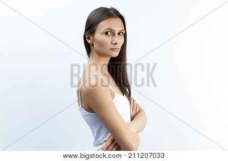 Studio portrait of young Caucasian woman with serious upset dissatisfied with a puzzled expression. arms crossed over the abdomen.