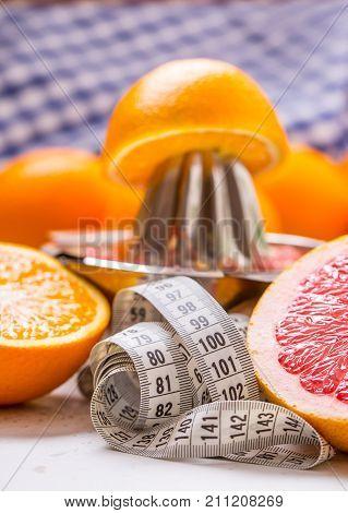Measure Tape And Juicer With Citrus Fruits. Preparation Of Orange Grape Or Multivitamin Juice, Hands