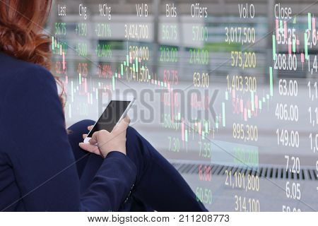 Double exposure of attractive young Asian businesswoman using mobile smart phone with stock market price and candlestick chart patterns uptrend background. Investment growth concept