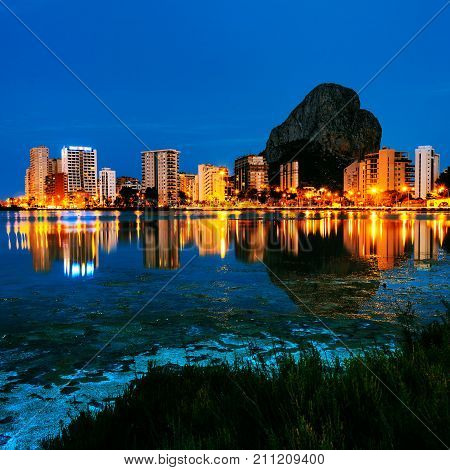 Costa Blanca Spain. Skyscrapers of Mediterranean summer resort Calpe in Costa Blanca Spain with reflection in the water of the lake Las Salinas. Penon de Ifach mountain at the background