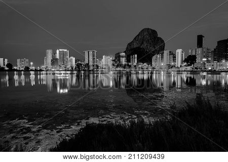 Costa Blanca Spain. Skyscrapers of Mediterranean summer resort Calpe in Costa Blanca Spain with reflection in the water of the lake Las Salinas. Penon de Ifach mountain. Black and white