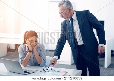 This should be done immediately. Side view on a mad boss pointing at a business document while standing next to his young employee and giving a good talk to her at work.