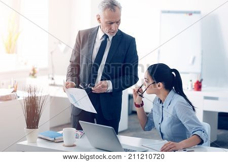 What is that. Confused young female employee taking off her glasses and looking at documents held by her mad boss trying to figure out why there is a mistake made by her.