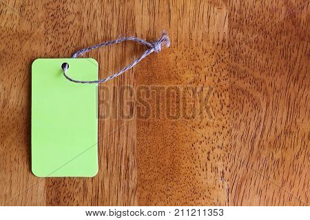 Blank yellow tag on a wooden background with copy space. Price tag sale label mockup.