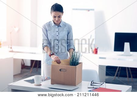 Getting fired. Emotionally exhausted young lady in smart casual standing next to her office table while putting her working supplies in a box and leaving her work.