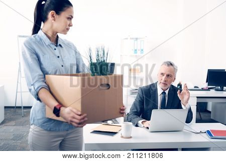 Saying goodbye. Selective focus on a mature boss looking at his serious female employee with a slight on his face and waving a farewell while a young lady leaving her work with a paper box in