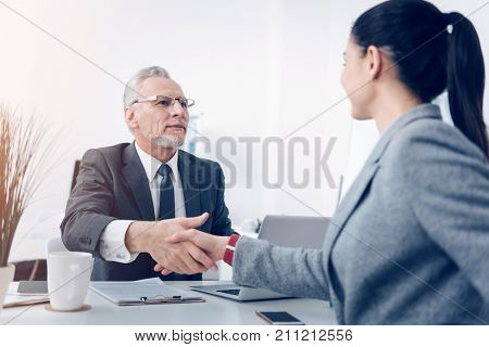 Nice job. Selective focus on a positive minded chief looking at his young up and coming employee with a slight smile on his face while both sitting at a table and shaking hands.