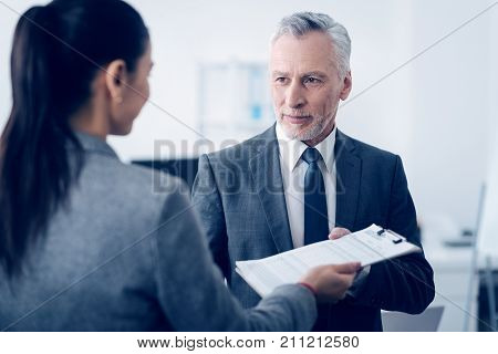 Trust and understanding. Selective focus on a mature boss looking at his young office worker with a slight smile on his face while taking a clipboard with a document brought by a female employee.