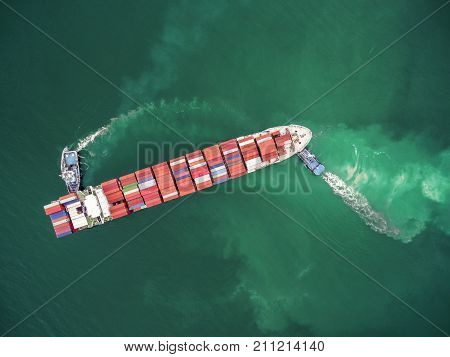two tug boat towing cargo container in warehouse harbor at thailand .