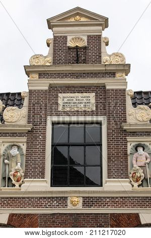 Top gable with memorial stone and sculptures of Huis van Achten in Alkmaar Netherlands
