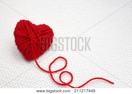 Red yarn ball like a heart on the white crochet background. Romantic Valentines Day or Christmas concept. Red heart made of wool yarn. Place for text copyspace