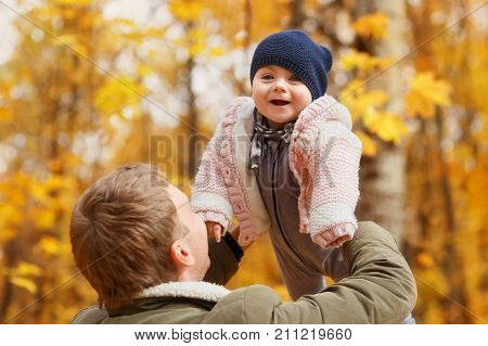 young father play with a little daughter in autumn park. Dad holding baby girl in hands. Happy family, paternal love, autumn season, outdoors concept