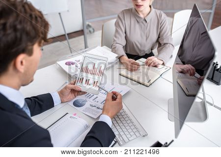 High angle of business people discussing statistics report looking at graphs and charts with financial data during meeting in modern office
