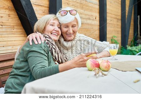 Pretty senior friends with charming toothy smiles embracing each other and remembering funny moments from their past while sitting at cozy small patio