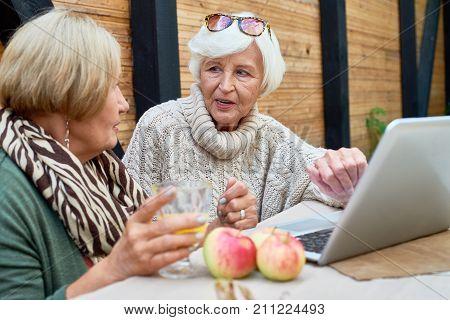 Tech-savvy senior women using modern laptop while sitting at outdoor cafe and enjoying freshly squeezed juice