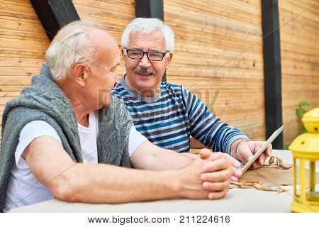 Two elderly friends gathered together at outdoor cafe and chatting animatedly with each other while waiting for their order