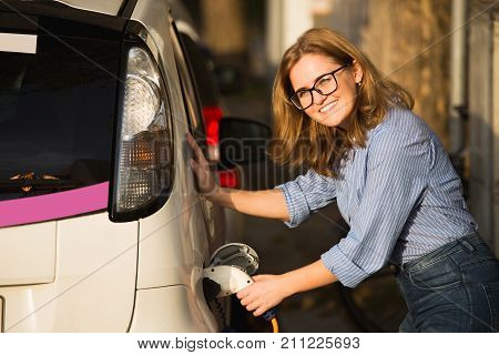 Young woman is charging an electric car. The rental car is charging at the charging station for electric vehicles. Car sharing.