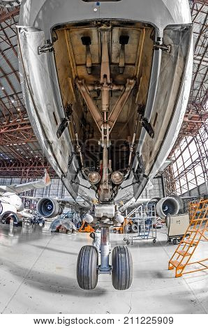 Large Passenger Aircraft On Service In An Aviation Hangar Rear View Of Front Landing Gear.