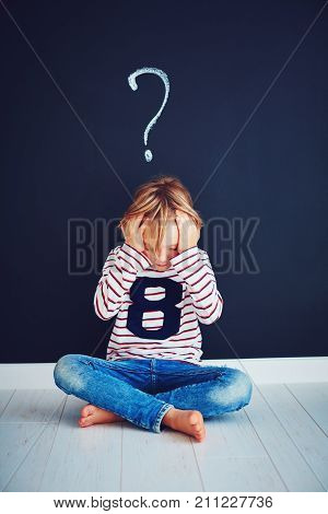 Sad, Frustrated School Boy Sitting On The Floor With Question Mark Above Him