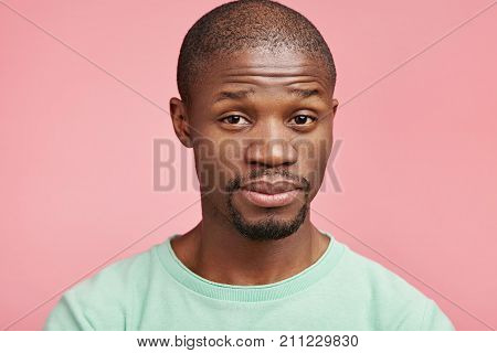 Indoor Portrait Of Serious Dissatisfied Puzzled Emotional Dark Skinned Man With Small Beard And Must