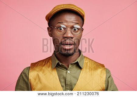 Indoor Picture Of Astonished Scared African Male In Fashionable Clothes, Opens Mouth Widely, Being H