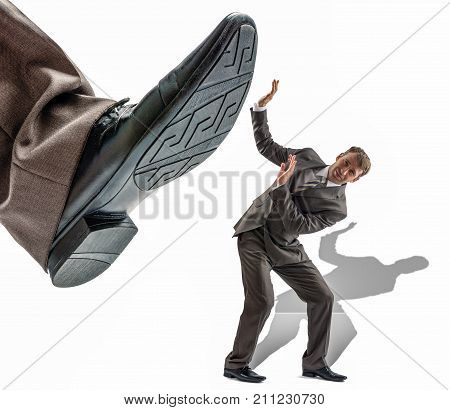 Small businessman is trampled by big foot in an empty space