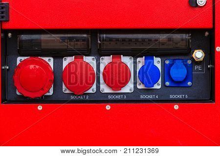 Electricity industrial safety concept. Electric plug with lapel flap fuse on red machine.