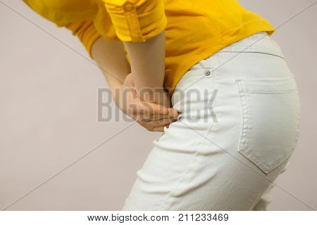 Closeup young sick woman with hands holding pressing her crotch lower abdomen. Medical or gynecological problems healthcare concept