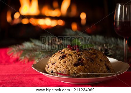 english christmas pudding with spoon. english christmas pudding with spoon. Traditional English steamed pudding with dried fruits and nuts for Christmas on the background of the fireplace