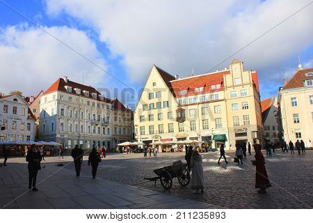 TALLINN, ESTONIA - OCTOBER 9, 2017: Town Hall Square (Raekoja plats) in Old Town of Tallinn. Historical european buildings with restaurants, bars, souvenir shop and people walking around at background
