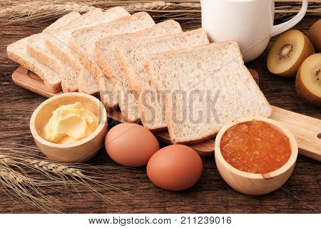 Slice whole wheat bread butter and orange jam on wooden table top.