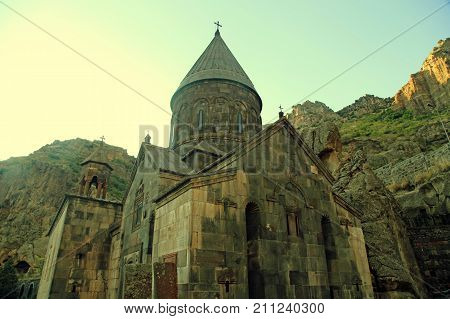 The ancient Christian temple Geghard in the mountains of Armenia. Sunset light