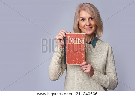 Old Female Teacher Holding An English Textbook