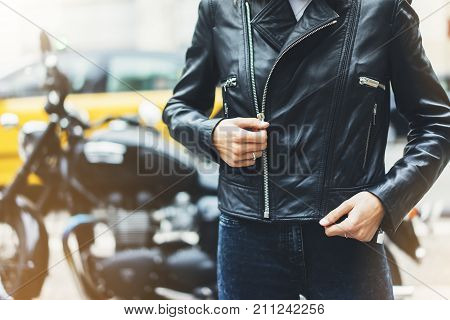 Girl unfastens black leather jacket on background motorcycle taxi in sun flare atmospheric city hipster biker female hands closeup motorbike street lifestyle traveler planing bike route in summer holiday concept