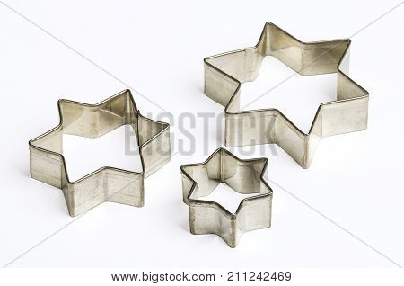 Three star shaped Christmas cookie cutters over white. Tin biscuit cutters, tool to cut cookie dough in particular shapes and to make cutouts. Hexagram shaped and six pointed geometric star figures.