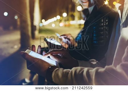 People together pointing finger on screen smartphone on background bokeh light in night atmospheric city group adult hipsters friends using in hands modern mobile phone closeup street online wi-fi internet concept