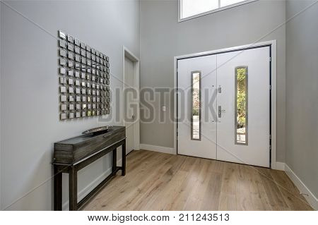 White Front Door Opens To A Contemporary Foyer