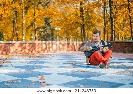 The young musician plays bass ukulele on the street. Man sitting on the ground with guitar. Concept. Basking