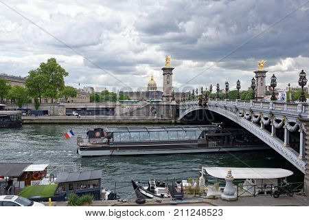 Paris; France-May 02; 2017: View of the Pont Alexandre lll. On the bridge are pedestrians and cars the ship sails under the bridge