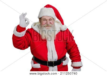 Cheerful Santa Claus man showing ok sign. Happy senior Santa Claus with ok sign on white background. Realistic Santa Claus, studio shot.