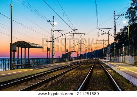 The railway station with the illuminated platform and the railroad going into the distance at twilight Sochi Russia