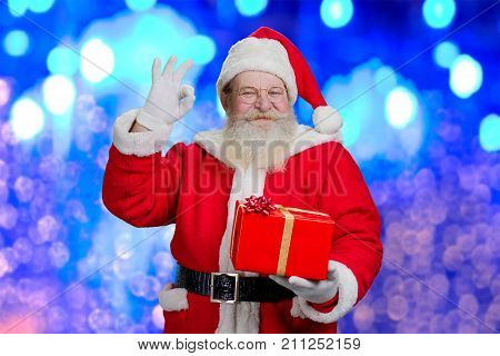 Happy Santa Claus with okey gesture. Portrait of cheerful Santa Claus with red present box in hand showing ok sigh with fingers, blue shimmering background.
