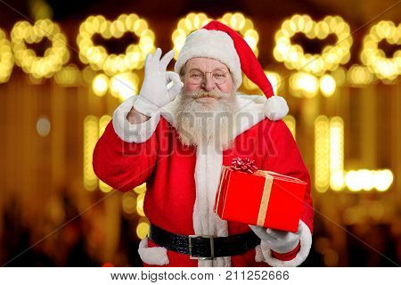 Smiling Santa Claus showing okey sign. Santa Claus with real beard holding Christmas present and making okey gesture with fingers on blurred background.
