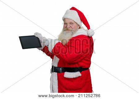 Santa Claus with computer tablet. Senior Santa Claus holding digital computer tablet and pointing on blank touch screen with index finger, white background.