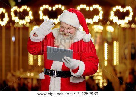Santa Claus gesturing with pc tablet. Senior santa Claus using digital tablet on festive shimmering background.
